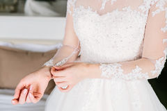 Bride is fasten sleeves on her dress, preparing for the wedding day. Close up Royalty Free Stock Images