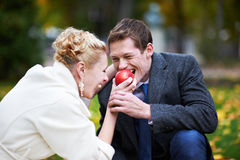 Bride feeds the groom a red apple Stock Images