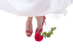 Bride feet in red shoes with rose Royalty Free Stock Image