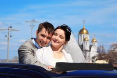 Bride with fiance against church Royalty Free Stock Image