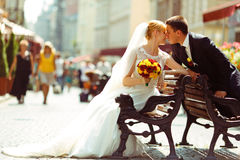 Bride and fiance kiss sitting on different old benches stock photos