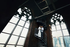 Bride and fiance standing on the spiral stairs in old Gothic cat Royalty Free Stock Photos