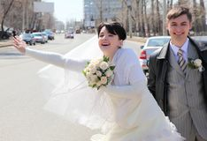 Bride with fiance on street stops car Stock Images