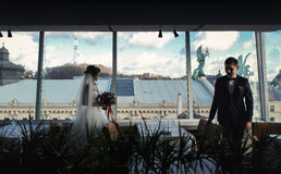 Bride and fiance walk between empty tables in restaurant with gr Stock Images