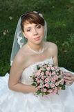 Bride with floral bouquet. Bride in dress and veil showing off her bouquet; looks as if she is ready to toss it stock photo
