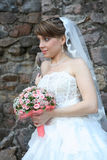 Bride with floral bouquet. Bride in dress and veil showing off her bouquet; looks as if she is ready to toss it royalty free stock image