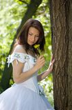 The bride with a flower. The bride has leant the elbows on a tree and smells a dandelion Royalty Free Stock Photography
