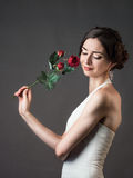 Bride with a flower. Beautiful woman with red roses Royalty Free Stock Image