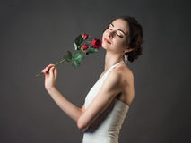 Bride with a flower. Beautiful woman with red roses Royalty Free Stock Images
