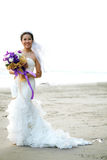 Bride with flower bouquet on the beach Stock Images