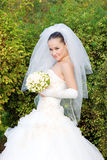 A bride with a flower bouquet outdoors Royalty Free Stock Photography
