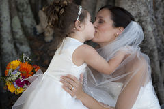 Bride and flower girl. Flower girl kissing bride sitting under a tree. Mother and daughter stock photo