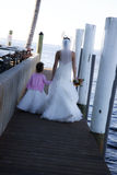 Bride and flower girl. Back view of flower girl and bride walking on dock Mother and daughter stock photography