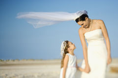 Bride and Flower Girl on Beach. Bride and a flower girl look at each other on a sandy beach. Horizontal shot stock image