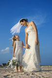 Bride and Flower Girl on Beach. Smiling bride looks down at a flower girl on the beach. Vertical shot stock photo