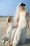 Bride and Flower Girl on Beach. Bride and a flower girl hold hands on a sandy beach. Horizontal shot stock images