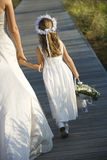 Bride and Flower Girl on Boardwalk. Cropped rear view of a bride walking and holding hands with a flower girl on the boardwalk. Vertical shot stock image