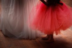 Bride and Flower Girl. A bride and flower girl standing on a hardwood floor showing only the bottom of their dresses and the flower girl`s bare feet stock photos