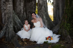 Bride and flower girl under tree. Bride and flower girl sitting under tree stock images