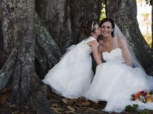 Bride and flower girl under tree. Flower girl kissing cheek of bride sitting under tree stock images