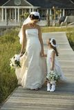 Bride and flower girl walking. Caucasian mid-adult bride holding hands with flower girl walking down wooden beach walkway stock photos