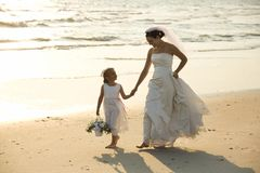 Bride and flower girl walking on beach. Caucasian mid-adult bride and flower girl holding hands walking barefoot on beach stock image