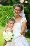 Bride with flower people daughter. Young mother and her daughter in front of the marriage.  the wedding day should be the most happy day in her life and her Royalty Free Stock Photo
