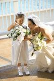 Bride and flowergirl. Caucasian mid-adult bride kneeling next to flower girl admiring her flowers