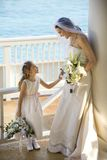 Bride and flowergirl. Caucasian mid-adult bride holding hands with flower girl Royalty Free Stock Photography