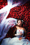 Bride in flowers. Woman in dressbride is lying in flowers on wedding Royalty Free Stock Photography