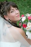 Bride with flowers. Bride sitting on the grass with flowers Royalty Free Stock Image