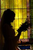 Bride With Flowers. Standing in front of a stained-glass window, a bride looks at her bouquet before walking down the aisle on her wedding day Stock Photography