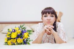 Bride with flowers. The bride with a bouquet of flowers lying on the bed Royalty Free Stock Images