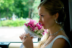 Bride with flowers in car Royalty Free Stock Photography