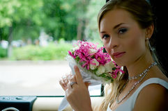 Bride with flowers in car Royalty Free Stock Photos