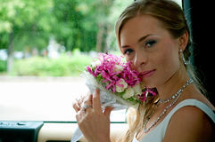 Bride with flowers in car Stock Photo