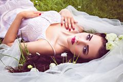 Bride with flowers in hair and veil lying on meadow Royalty Free Stock Photos