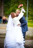 Bride with flowers hugging groom around neck Royalty Free Stock Photography