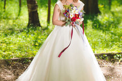 Bride with Flowers in Park Stock Image