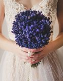 Bride with Flowers. Bride wearing white dress holding beautiful bouquet of purple flowers Stock Images