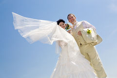 Bride with flying viel and groom Stock Images