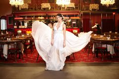 Bride in flying wedding dress in the restaurant Stock Photo