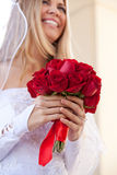 Bride with focus on her Red Rose Bouquet. A Bride holding a Beautiful Red Rose Bouquet Royalty Free Stock Images