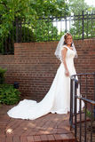 Bride in front of a brick wall. Bride with wedding dress in front of a brick wall Stock Photo