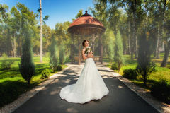 Bride in front of pavillion in park. Beautiful bride in front of decorative pavillion in summer park Stock Images