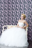 Bride full length sitting portrait. 20s yeared bride is sitting on a bench with the smile on her face Stock Image