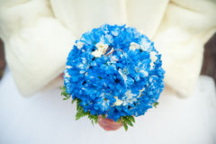 Bride in a fur coat holding a bouquet which lie wedding rings Stock Images
