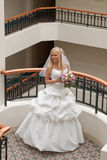 Bride in gallery. Beautiful blonde bride with bunch of flowers in the gallery Stock Image