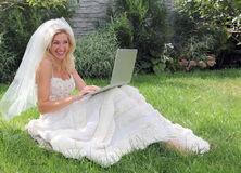 The bride in the garden. A bride using a laptop Royalty Free Stock Photography