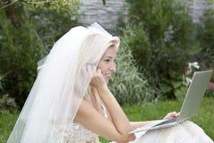 The bride in the garden. A bride using a laptop Stock Photo
